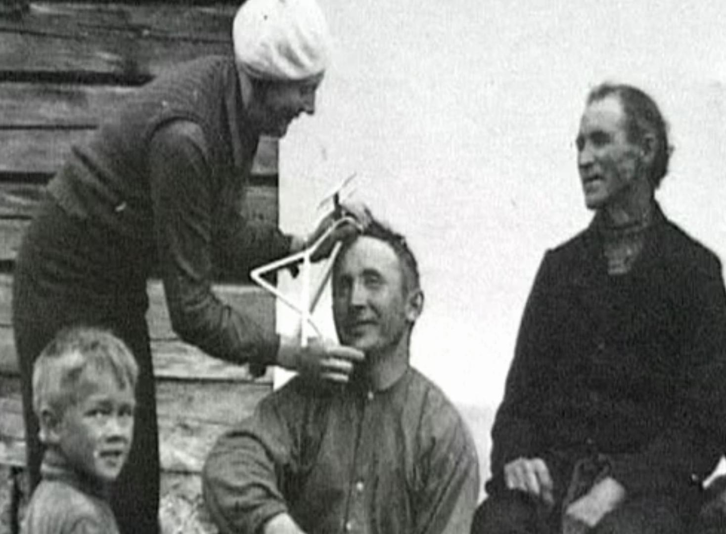 Ett gammalt fotografi där man mäter en persons skalle